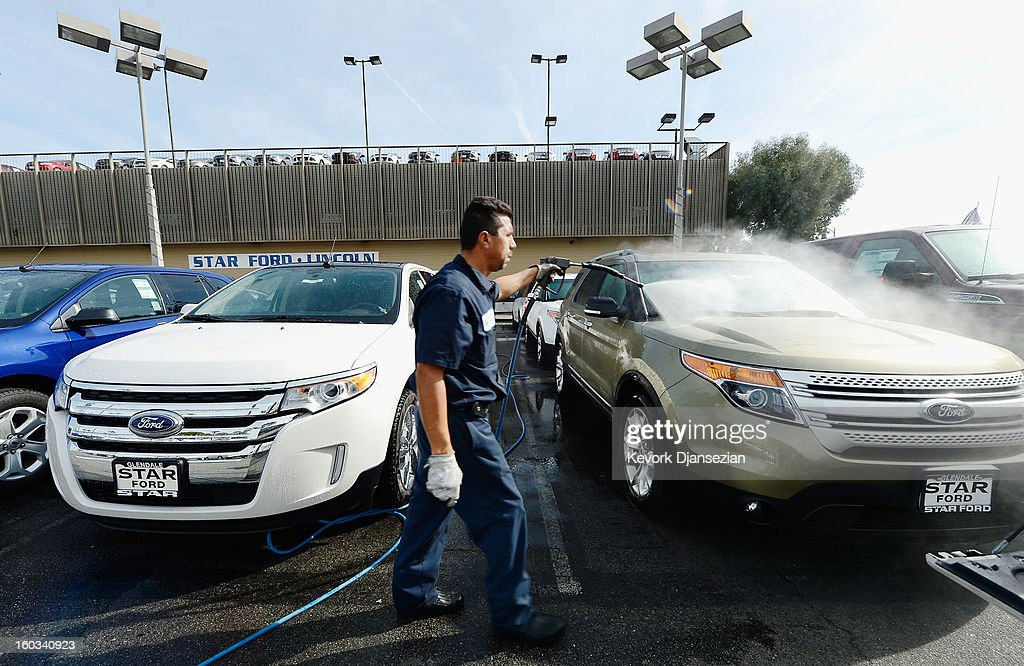 A worker cleans Ford SUV's at Star Ford dealership sign on January 29, 2013 in Glendale, California. According to reports the nation's second-largest automaker earned $1.7 billion in the fourth-quarter quarter, the highest pre-tax profit in a decade, up 55% from a year earlier. For the year, earnings slipped 5% to $5.7 billion.