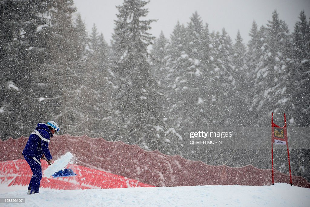 A worker cleans fresh snow before the Men's downhill world cup, on December 15, 2012 in Val Gardena. Steve Nyman of USA (C) won the race front of Slovenia's Rok Perko (L) and Canda's Erik Guay 3rd place.