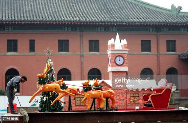 A worker cleans next to a Christmas decoration on December 7 2006 in Chongqing Municipality China Western traditions such as the Christmas Day...