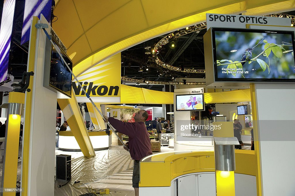 A worker cleans Nikon Corp. signage prior to the 2013 Consumer Electronic Show in Las Vegas, Nevada, U.S., on Monday, Jan. 7, 2013. The 2013 CES trade show, which runs until Jan. 11, is the world's largest annual innovation event that offers an array of entrepreneur focused exhibits, events and conference sessions for technology entrepreneurs. Photographer: David Paul Morris/Bloomberg via Getty Images