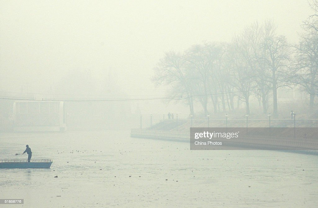 A worker cleans on a river in heavy fog December 14, 2004 in Beijing, China. The heaviest fog since winter has in some areas reduced visibility is to less than 10 meters (11 yards).