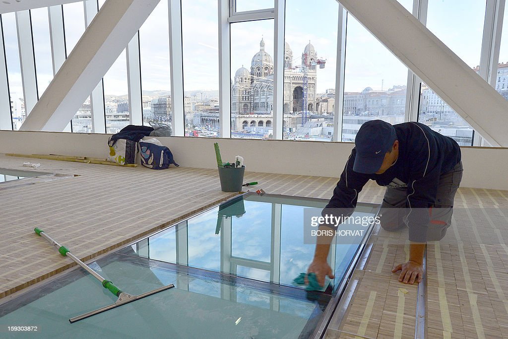 A worker cleans on January 11, 2013 a window in the 'Centre Regional de la Mediterranee' (Mediterranean Regional Centre), designed by Italian architect Stefano Boeri. Long plagued by a reputation for gang crime and lawlessness, France's port city of Marseille is hoping its year as the 2013 European Capital of Culture will finally give its image a makeover. The gritty Mediterranean city will kick off the festivities on January 12, 2013 with a downtown parade, fireworks and the opening of a slew of exhibitions.