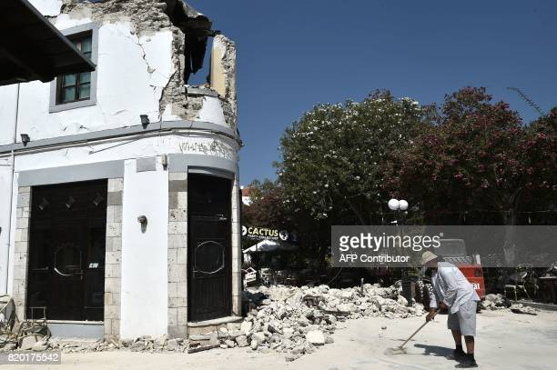 A worker cleans outside a bar where two tourists were killed following a 65 magnitude earthquake which struck the region on July 21 2017 Two...