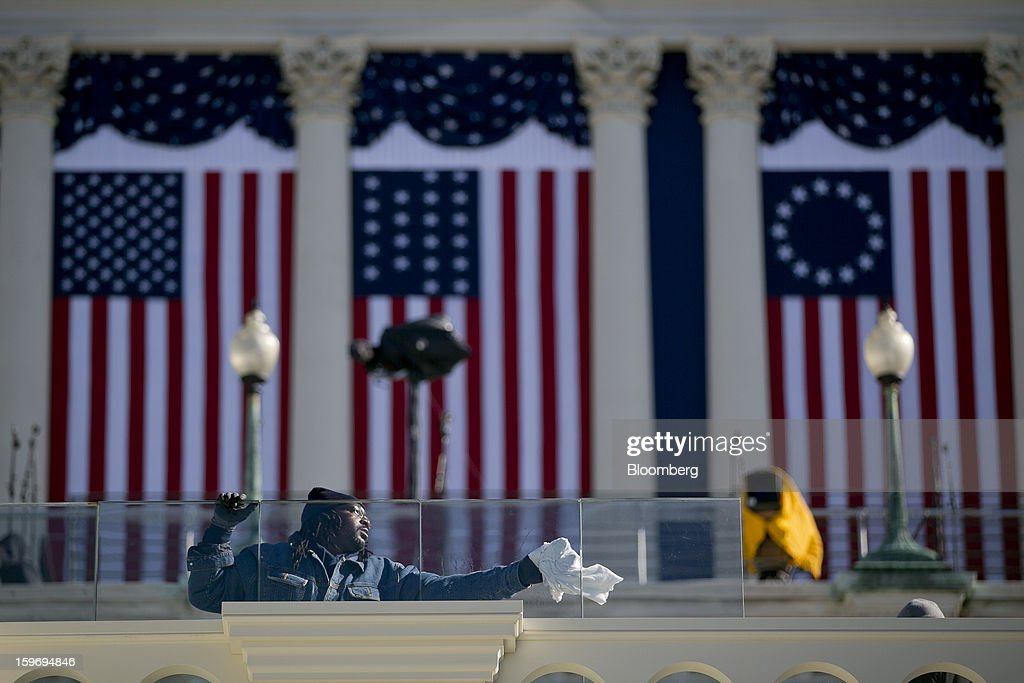 A worker cleans the bulletproof glass that surrounds the inaugural platform outside the U.S. Capitol prior to the second inauguration of U.S. President Barack Obama in Washington, D.C., U.S., on Friday, Jan. 18, 2013. President Obama's second inauguration next week will combine the star power of Beyonce, Kelly Clarkson and James Taylor with a lineup that reflects social values Obama will champion in his new term. Photographer: Andrew Harrer/Bloomberg via Getty Images