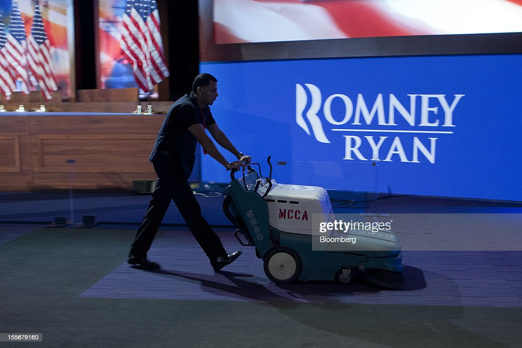 A worker cleans the carpet inside the ballroom where Republican presidential candidate Mitt Romney is scheduled to speak at the Boston Convention and Exhibition Center in Boston, Massachusetts, U.S., on Tuesday, Nov. 6, 2012. U.S. President Obama is seeking to overcome the drag of high unemployment and economic weakness that has frustrated predecessors' re-election bids, while his Republican rival Mitt Romney reaches for an upset to propel him beyond his party's standing and swamp an electoral map stacked against him on the final day of the presidential race. Photographer: Andrew Harrer/Bloomberg via Getty Images