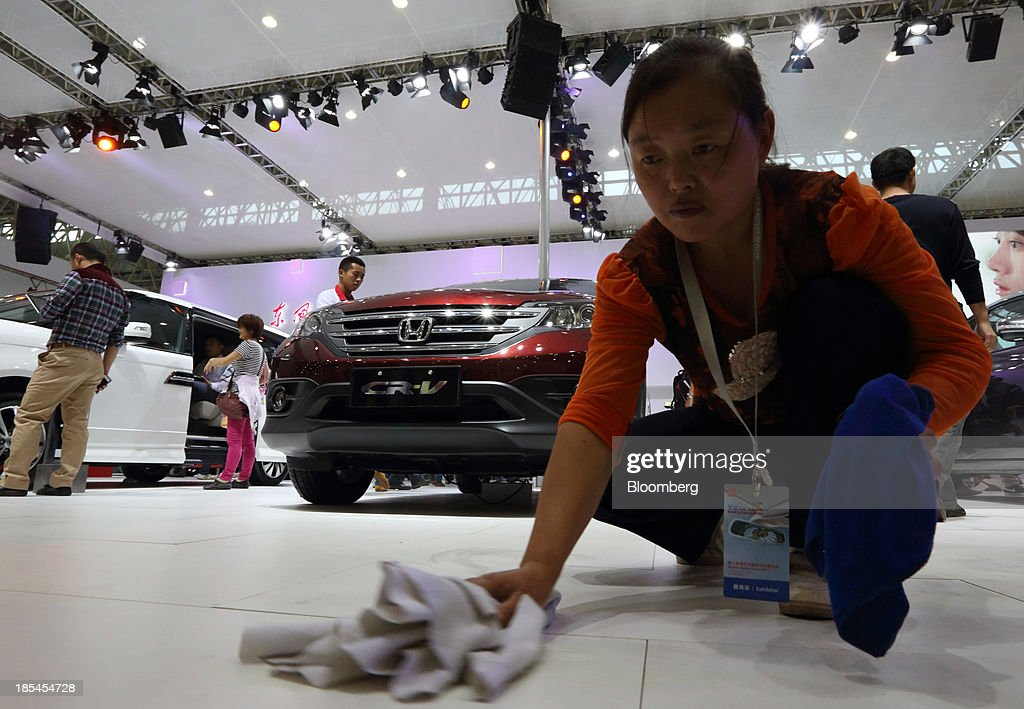 A worker cleans the floor in front of a Honda CR-V vehicle manufactured by Dongfeng Honda Automobile Co., the joint venture between Dongfeng Motor Corp. and Honda Motor Co., at the Wuhan Motor Show 2013 in Wuhan, China, on Saturday, Oct. 19, 2013. The show will be held through Oct. 23. Photographer: Tomohiro Ohsumi/Bloomberg via Getty Images