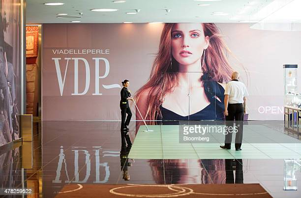 A worker cleans the floor near a Via Delle Perle fashion advertisement at the Esentai luxury shopping mall in Almaty Kazakhstan on Tuesday June 23...