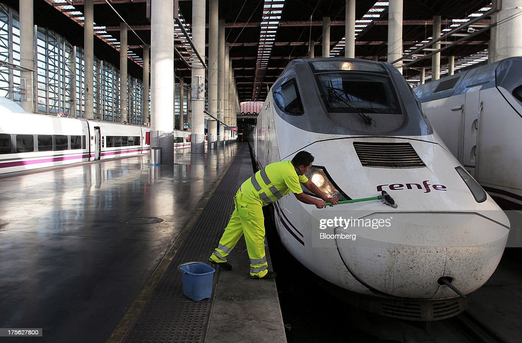 A worker cleans the front of an Alta Velocidad Espanola (AVE) high-speed train operated by Renfe Operadora SC as it sits at a platform at Atocha train station in Madrid, Spain, on Saturday, Aug. 3, 2013. Spain's state-owned rail operator Renfe plans to cut almost 500 jobs, or 4% of staff, as early as this year, ABC reports, citing comments by Public Works Minister Ana Pastor. Photographer: Antonio Heredia/Bloomberg via Getty Images