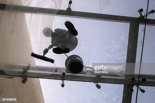 A worker cleans the glass canopy outside the newly built Terminal 2 of the Chhatrapati Shivaji International Airport operated by GVK Power...