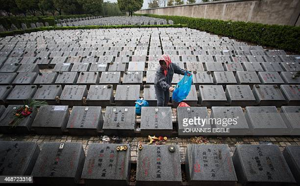 A worker cleans the graves during the annual 'Qingming' festival or Tomb Sweeping Day at a public cemetery in Shanghai on April 6 2015 During...