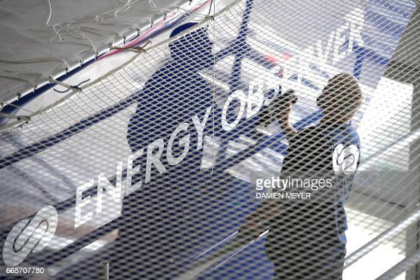 A worker cleans the logo of self energy producer multihull 'Energy Observer' on April 4 2017 in SaintMalo western France The Energy Observer an...