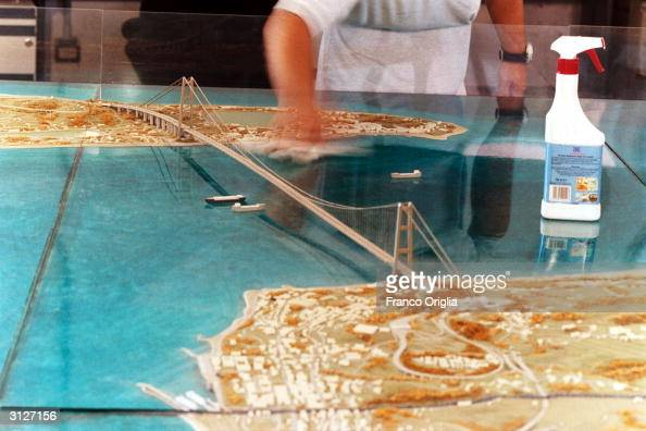 A worker cleans the plastic of a scale design of the planned bridge over the Strait of Messina designed by Pininfarina is shown March 24 2004 in Rome...