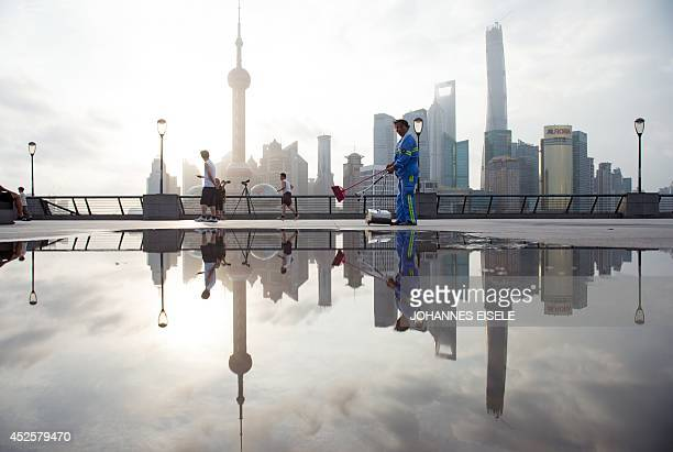 A worker cleans the promenade on the Bund along the Huangpu River against the skyline of the Lujiazui Financial District in Pudong in Shanghai on...
