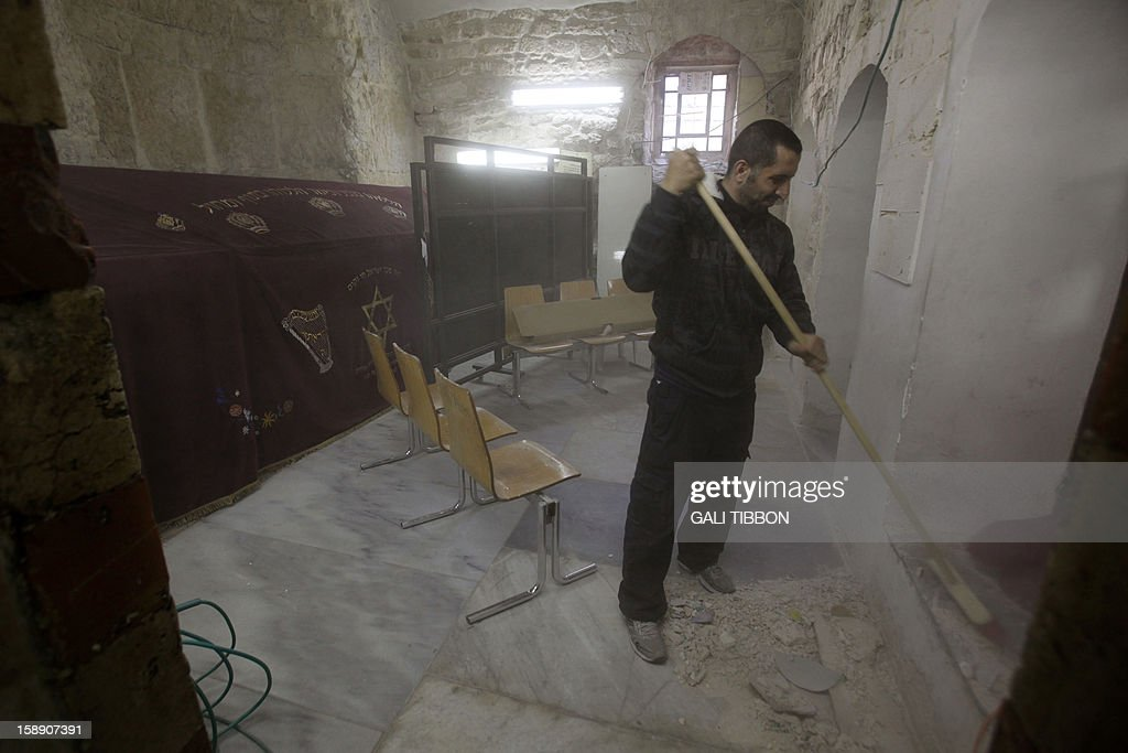 A worker cleans the rubble at King David's Tomb on Mount Zion in Jerusalem on January 3, 2013 after vandals smashed the 17th-century ceramic tiles decorating the Tomb. King David's Tomb is an ancient building sacred to the three monotheistic faiths. The lower part houses the traditional tomb of King David, while the Room of the Last Supper occupies the second floor, where according to Christian faith it is believed to be the site where Jesus celebrated Passover with his disciples before the crucifixion. AFP PHOTO/GALI TIBBON