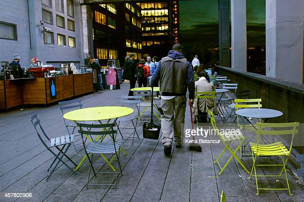 A worker cleans the seating area near the Blue Bottle Coffee stand on the High Line on October 24 2014 in New York City Dr Craig Spencer who returned...