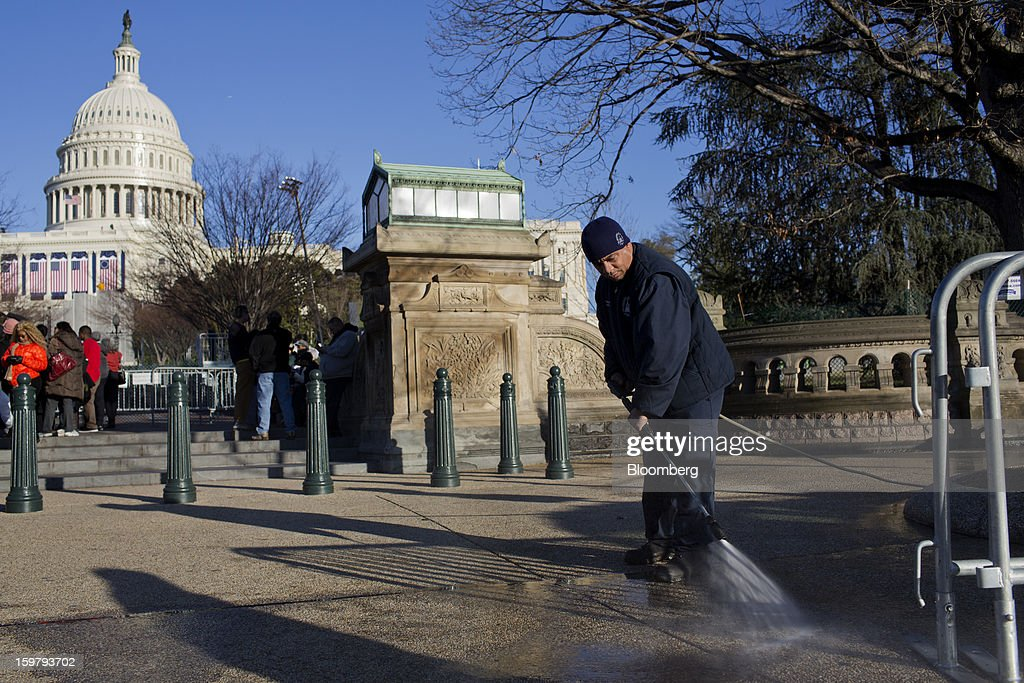 A worker cleans the sidewalk in front of the Capitol building ahead of the presidential inauguration in Washington, D.C., U.S., on Sunday, Jan. 20, 2013. As he enters his second term U.S. President Barack Obama has shed the aura of a hopeful consensus builder determined to break partisan gridlock and adopted a more confrontational stance with Republicans. Photographer: Victor J. Blue/Bloomberg via Getty Images
