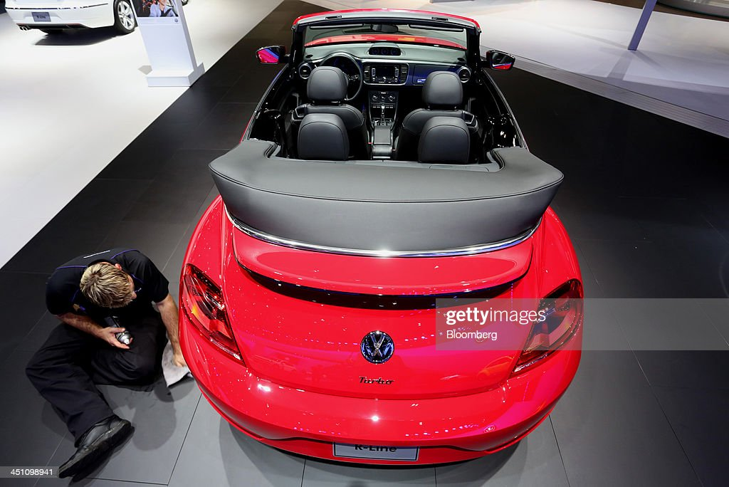 A worker cleans the tire of a Volkswagen AG Beetle R-Line convertible vehicle displayed during the LA Auto Show in Los Angeles, California, U.S., on Thursday, Nov. 21, 2013. The 2013 LA Auto Show is open to the public Nov. 22 - Dec. 1. Photographer: Jonathan Alcorn/Bloomberg via Getty Images