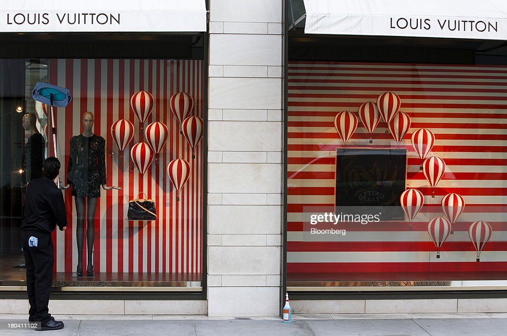 A worker cleans the window of a LVMH Moet Hennessy Louis Vuitton SA store on Rodeo Drive in Beverly Hills, California, U.S., on Wednesday, Sept. 11, 2013. The U.S. Census Bureau is scheduled to release retail sales figures on Sept. 13. Photographer: Patrick T. Fallon/Bloomberg via Getty Images