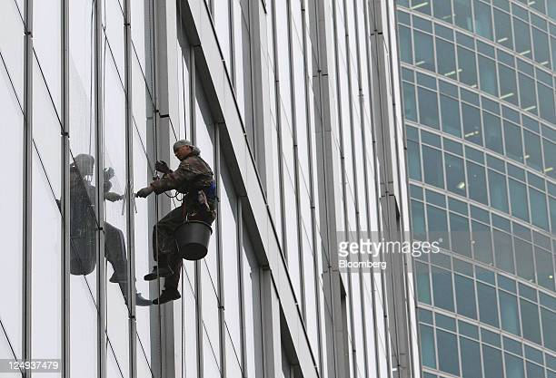 A worker cleans the windows of a skyscraper at the Moscow International Business Center also known as MoscowCity the capital's new commercial...