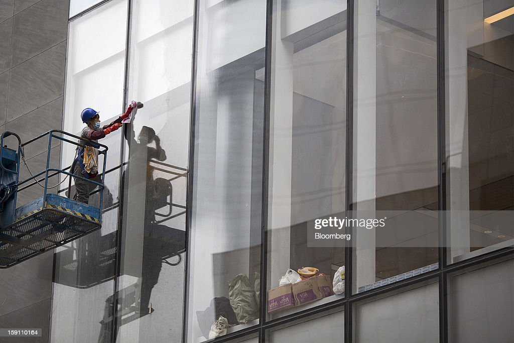 A worker cleans the windows of CCB Tower, which houses the local operations of China Construction Bank Corp., in the central business district of Hong Kong, China, on Friday, Jan. 4, 2013. Hong Kong topped the ranks as the most expensive office market by total occupancy cost, according to a report by CBRE Research released on Jan. 7. Photographer: Jerome Favre/Bloomberg via Getty Images