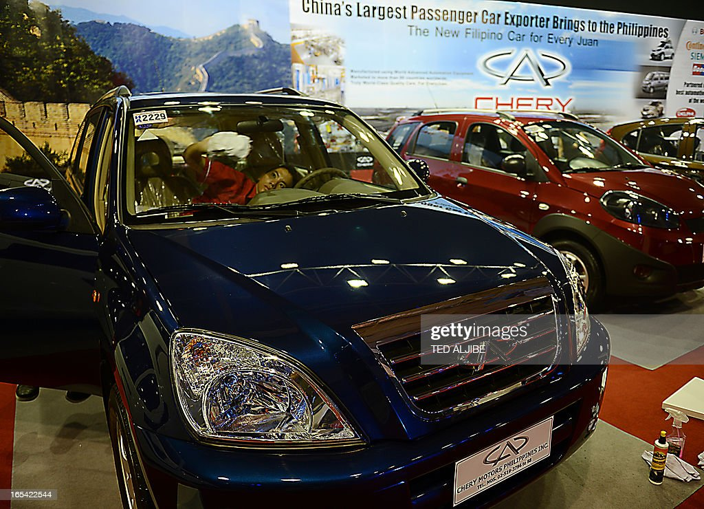 A worker cleans the windshield of one of China's car manufacturer Chery vehicle displayed at the auto show in Manila on April 4, 2013. The annual auto show is being held from April 4 to 7, at the world trade center.