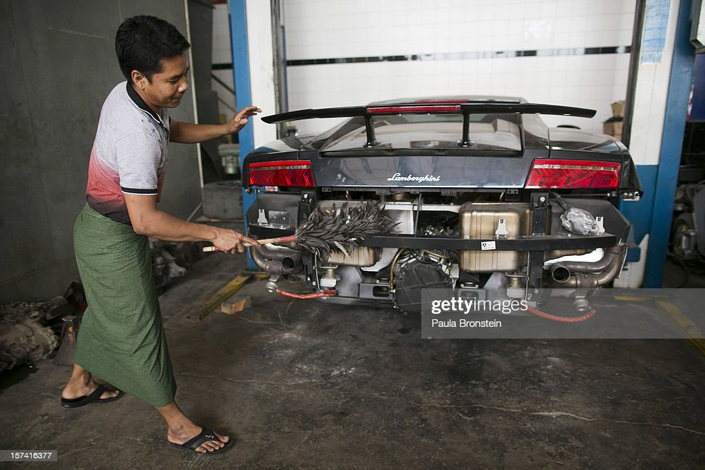 A worker cleans up a Lamborghini, which is waiting for car parts at the Htoo Auto Service workshop November 29, 2012 Yangon, Myanmar. IImport restrictions have been eased, resulting in many new cars seen on the streets. Most of the cars are being imported from Japan. In the past importing cars had been strictly limited under the military government until last year. Previously only the ruling elite, politicians and military personnel could obtain permission to import foreign cars.