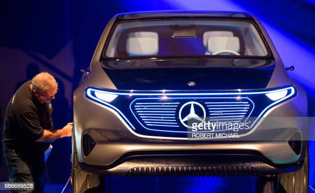 A worker cleans up a prototype of a MercedesBenz car as preparations are under way for the groundbreaking ceremony for a new plant of the ACCUMOTIVE...