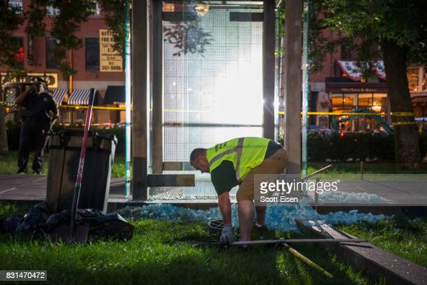 A worker cleans up broken glass at the New England Holocaust Memorial that was vandalized when a rock was thrown through a panel that was part of it...