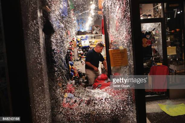 A worker cleans up broken glass from a window smashed during a protest of the acquittal of former St Louis police officer Jason Stockley on September...