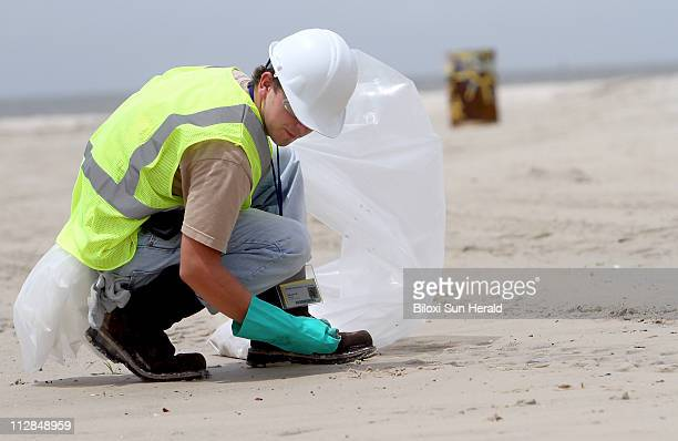 A worker cleans up debris while looking for tar balls on the beach in Gulfport Mississippi on Tuesday July 6 2010