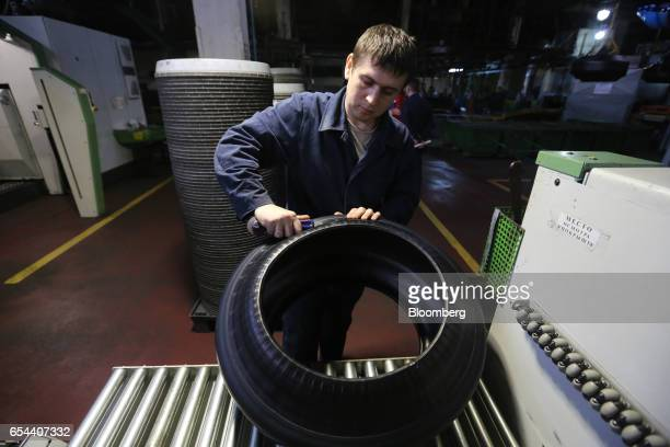 A worker cleans up the edge of a 'green' tire after shaping on a machine at the Belshina JSC tire factory in Babruysk Belarus on Thursday March 16...