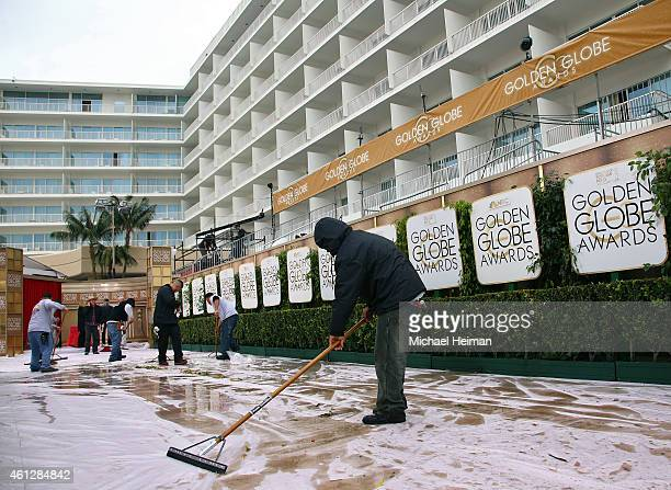 Worker clear water off of a tarp covered red carpet as preparations continue ahead of the 72nd Annual Golden Globe Awards at The Beverly Hilton Hotel...
