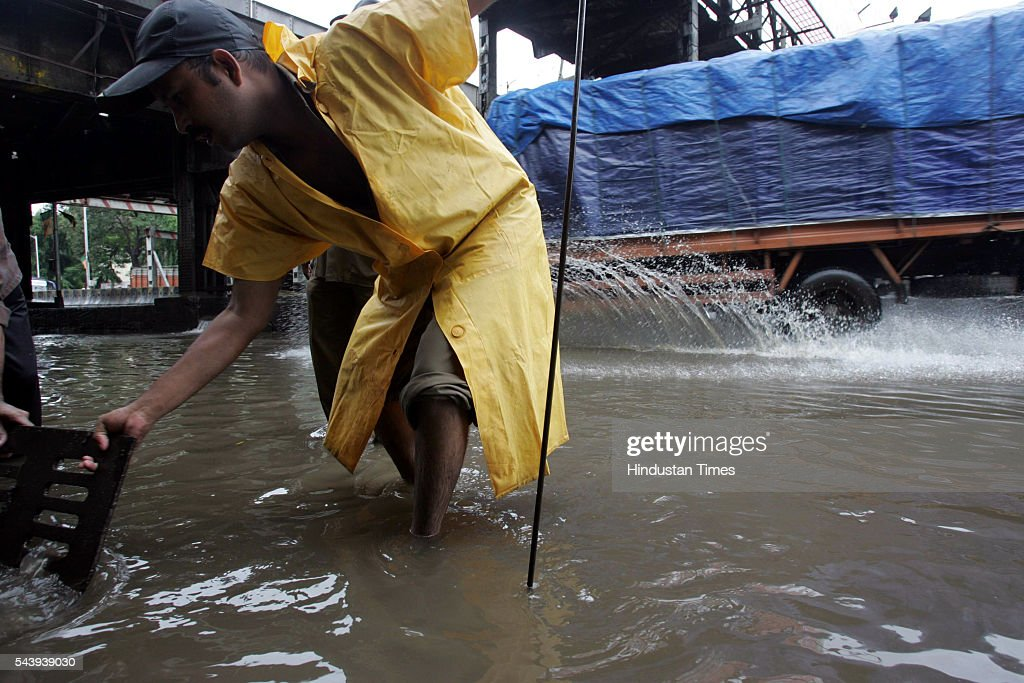 BMC worker clearing the drainage line for rain water to discharge freely at Kings Circle on July 31, 2005 in Mumbai, India.
