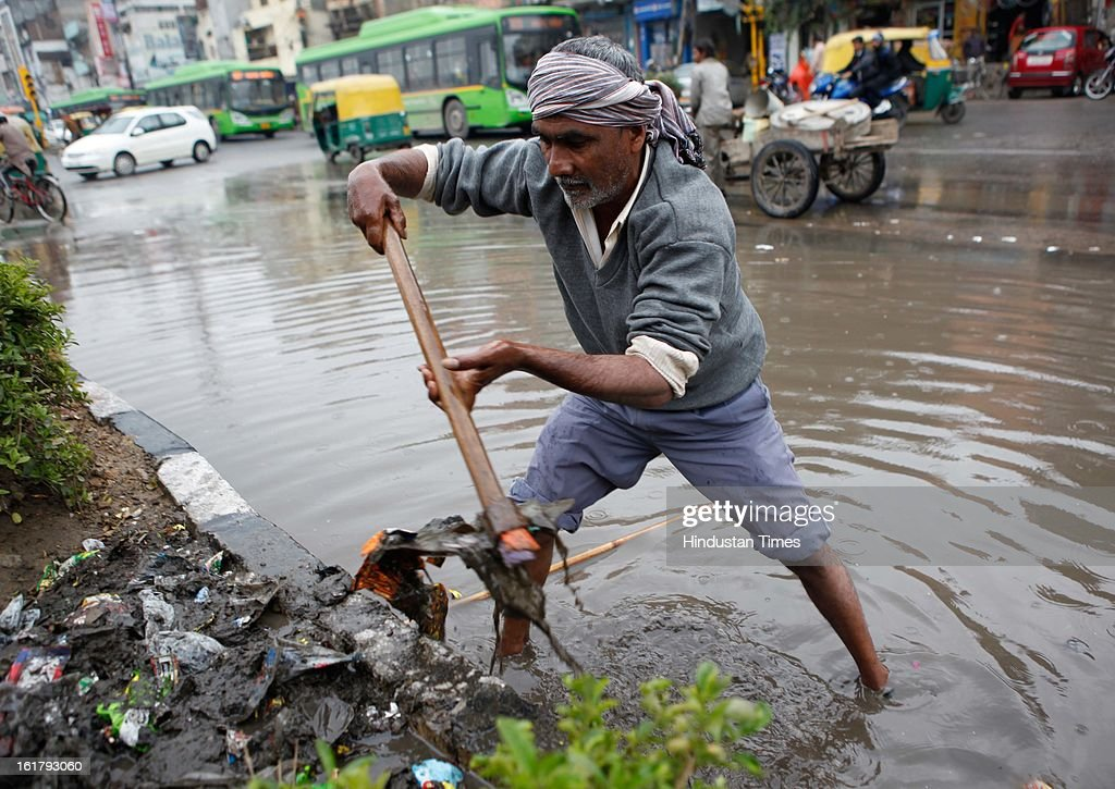 MCD worker clearing waterlogged road near mother dairy as it rains with overcast sky on February 16, 2013 in New Delhi, India. The National capital witnessed a total of 18.6 mm of rains since yesterday and the weather is likely to remain cloudy for another day.