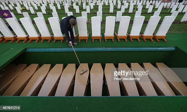 A worker clears leaves from coffins containing the remains of 15 British World War One soldiers at the Commonwealth War Graves Commission YFarm...