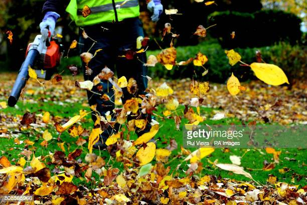 A worker clears leaves with a leaf blower in Swadlincote south Derbyshire during autumn