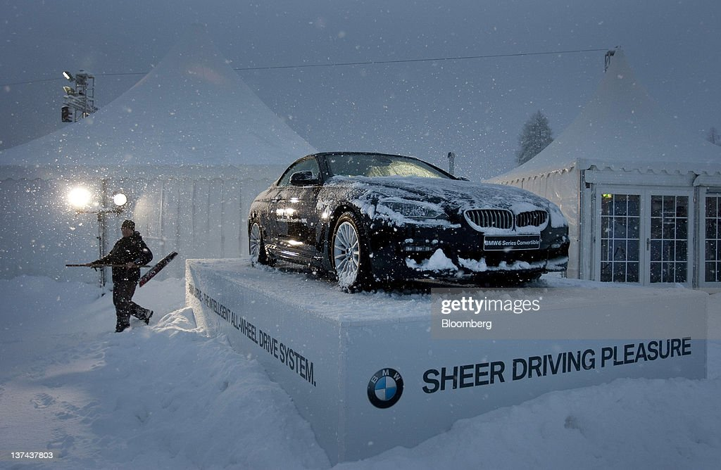 A worker clears snow from a Bayerische Motoren Werke AG (BMW) vehicle on display at the annual Klosters Snow Polo event in Klosters, Switzerland, on Friday, Jan. 20, 2012. German Chancellor Angela Merkel will open next week's World Economic Forum in Davos, Switzerland, which will be attended by policy makers and business leaders including U.S. Treasury Secretary Timothy F. Geithner. Photographer: Scott Eells/Bloomberg via Getty Images
