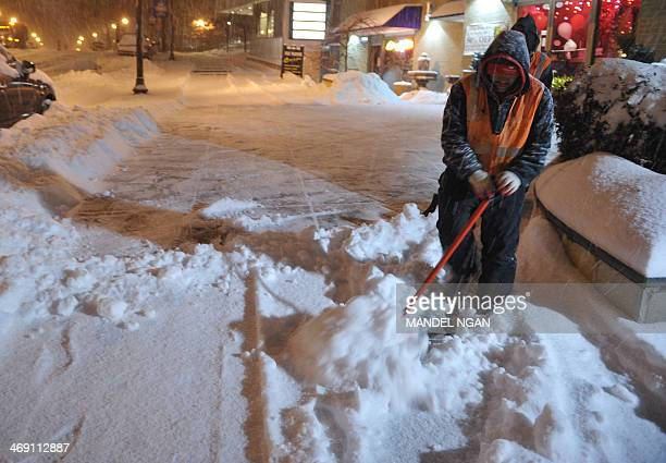 A worker clears snow from a sidewalk in Chevy Chase Maryland in the early hours of February 13 2014 A deadly ice storm stranded scores of people on...