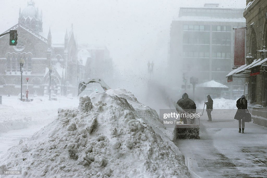 A worker clears snow from a sidewalk in the Back Bay neighborhood during a lingering blizzard on February 9, 2013 in Boston, Massachusetts. The powerful storm has knocked out power to 650,000 and dumped more than two feet of snow in parts of New England.