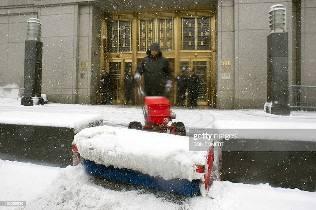 A worker clears snow outside the Federal Courthouse in Manhattan March 8, 2013 in New York. Inside the court the son-in law of Osama bin Laden,Sulaiman Abu Ghaith , pleaded not guilty Friday to charges of terrorism which he was formally charged by a New York court. The New York judge has ordered that Abu Gaith, who wore a short gray beard, 'remains in custody' until the next hearing scheduled for April 8.