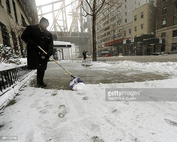 A worker clears the sidewalk on the Upper East Side of New York March 2 2009 as a massive winter storm hit the Northeast canceling hundreds of...