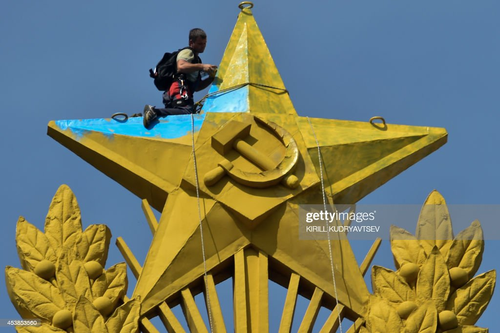 A worker climber repaints in yellow a blue star at the top of a Stalinera skyscraper in Moscow on August 20 2014 This giant star was painted in...