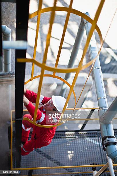 Worker climbing ladder at oil refinery