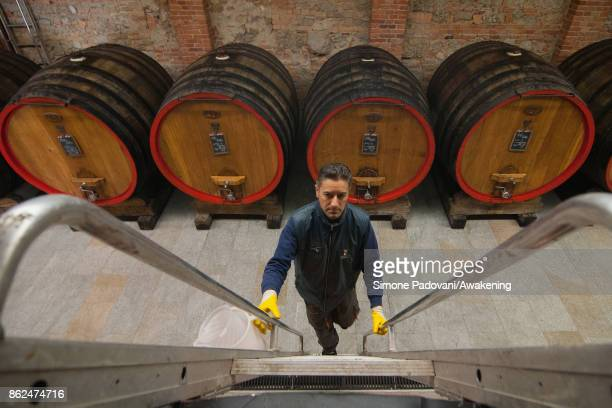 A worker climbs a barrel with Barolo to check it on October 17 2017 in the Barolo region Italy Because of the high summer temperatures Barolo's...