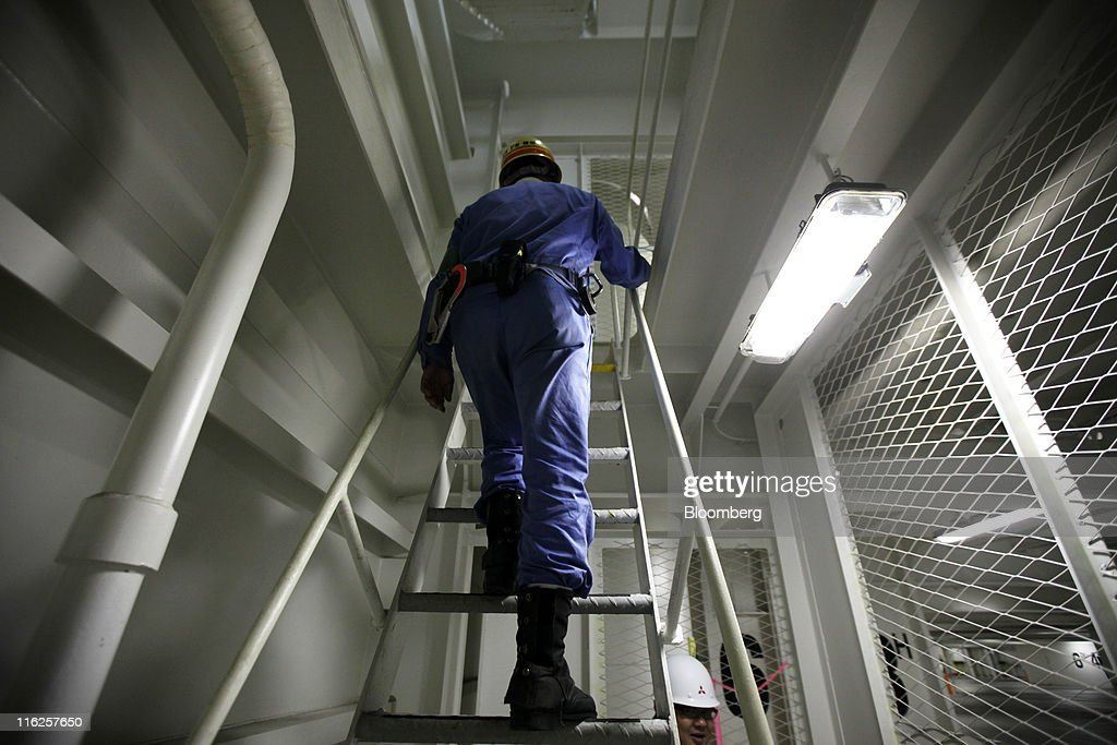 A worker climbs a ladder in the Nippon Yusen K.K.'s car transporter ship, Auriga Leader, at Mitsubishi Heavy Industries Ltd.'s Honmoku plant in Yokohama city, Kanagawa prefecture, Japan, on Wednesday, June 15, 2011. Nippon Yusen K.K. is Japan's largest shipping line. Photographer: Tomohiro Ohsumi/Bloomberg via Getty Images