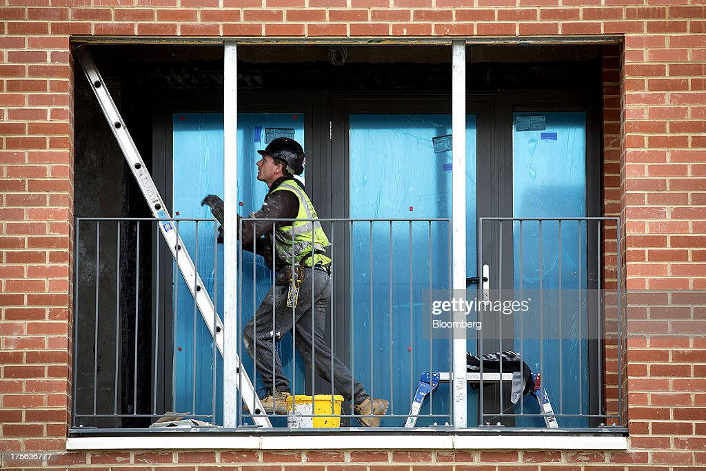 A worker climbs a ladder on a balcony at the Oval Quarter, a shared ownership, private and social residential housing complex developed by Higgins Group Plc in partnership with Nottinghill Housing and Pinnacle Regeneration Group, in London, U.K., on Monday, Aug. 5, 2013. U.K. house prices rose 0.8 percent in July, from 0.3 percent the previous month, Nationwide Building Society said. Photographer: Simon Dawson/Bloomberg via Getty Images