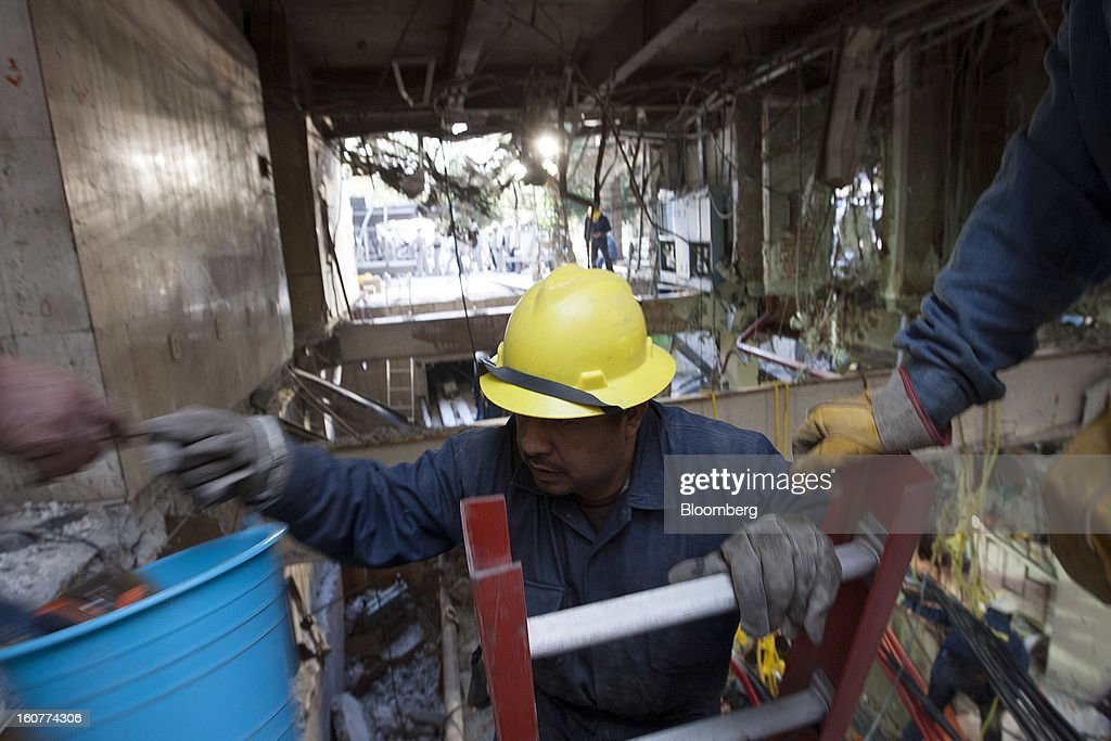 A worker climbs a ladder to bring up some rubble during cleanup operations at the Petroleos Mexicanos headquarters building in Mexico City, Mexico, on Tuesday, Feb. 5, 2013. Mexican authorities said a buildup of gas led to the blast last week that killed 37 people at Petroleos Mexicanos's headquarters, the first official attempt to explain the nation's deadliest explosion since 2006. Photographer: Susana Gonzalez/Bloomberg via Getty Images