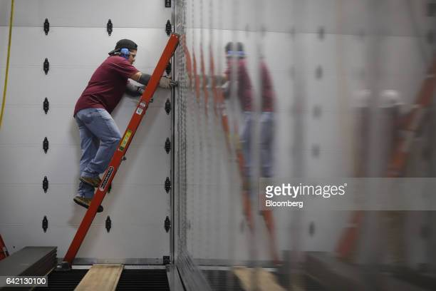A worker climbs a ladder while installing rivets inside a semi trailer on the factory floor at the Wabash National Corp manufacturing facility in...
