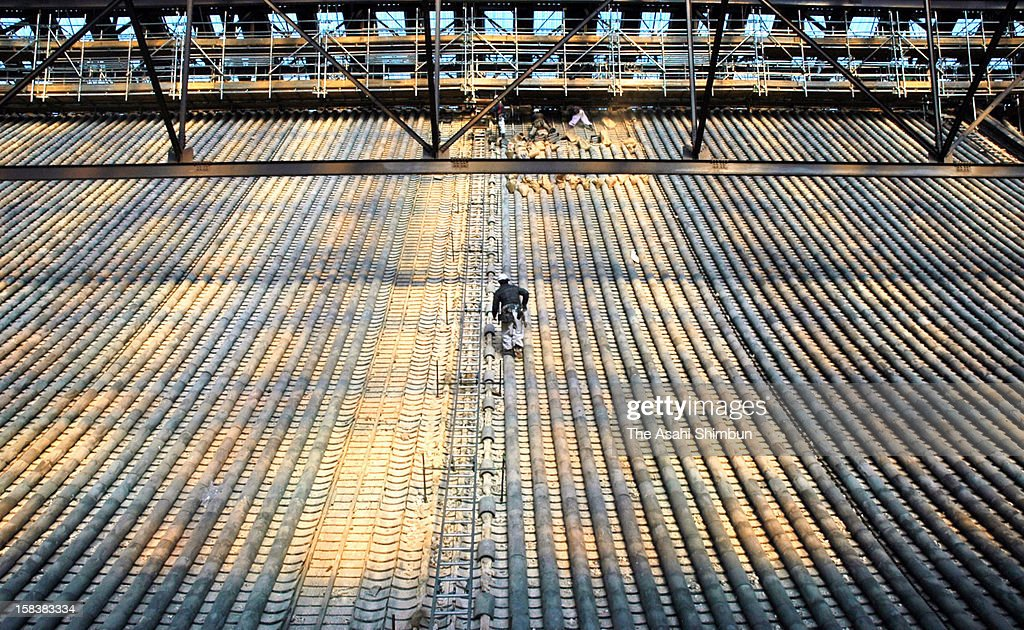 A worker climbs the roof of Mieido hall as the tile removal work begins at Chion-In temple on December 13, 2012 in Kyoto, Japan. The renovation continues by the end of 2018.