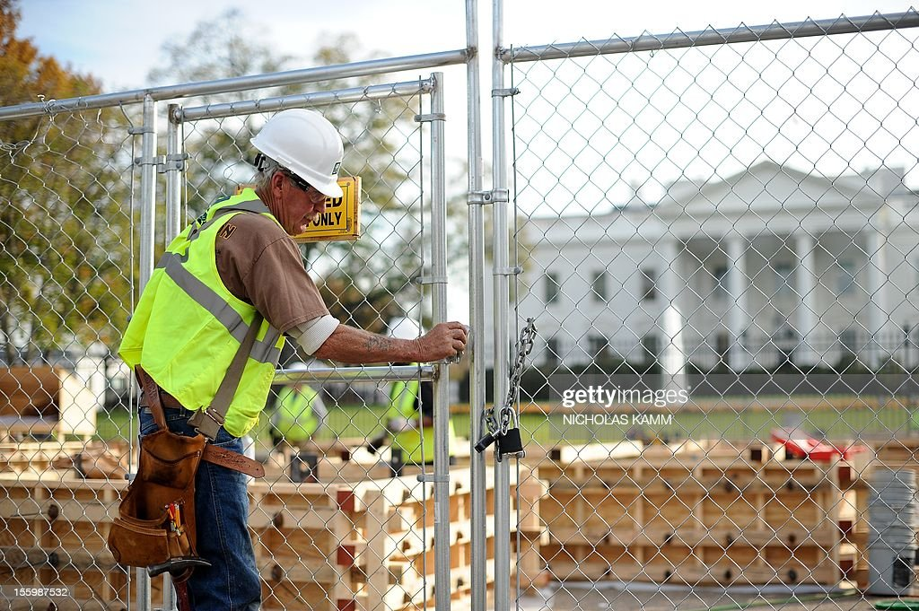 A worker closes a gate as construction for US President Barack Obama's second inauguration is under way in front of the White House in Washington on November 10, 2012. Obama won Florida's 29 electoral votes in the presidential election on November 10, further fattening his substantial margin of victory in what had been predicted to be a close race. The state was the last to report its tally from the election November 6, in which Obama beat Republican Mitt Romney. With Florida's votes in the electoral college, the president's total goes up to 332, against 206 for Romney. AFP PHOTO/Nicholas KAMM